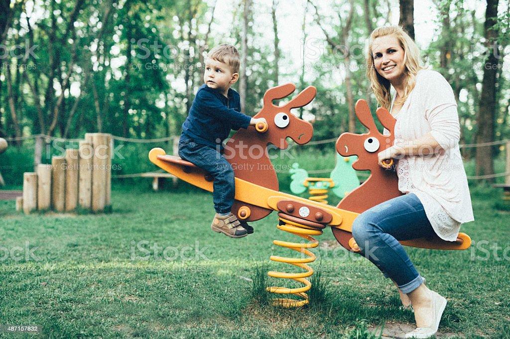 Madre e hijo jugando en el patio de juegos - foto de stock