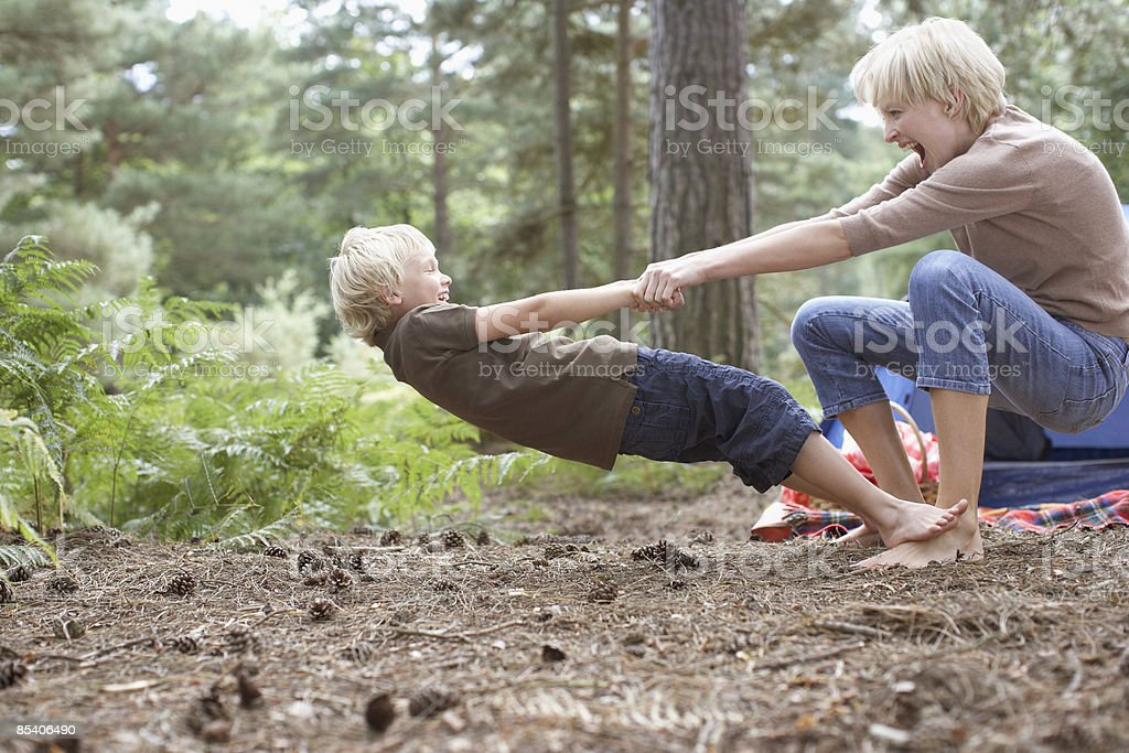 Mother and son playing in woods stock photo
