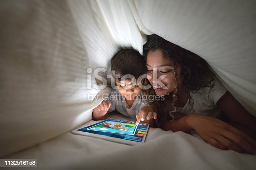 Portrait of a happy mother and son playing on a digital tablet in bed and smiling under the covers