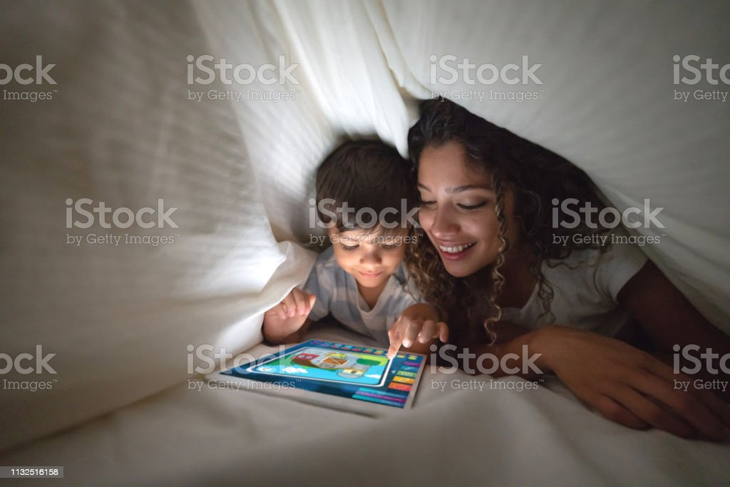 Mother and son playing on a digital tablet in bed stock photo