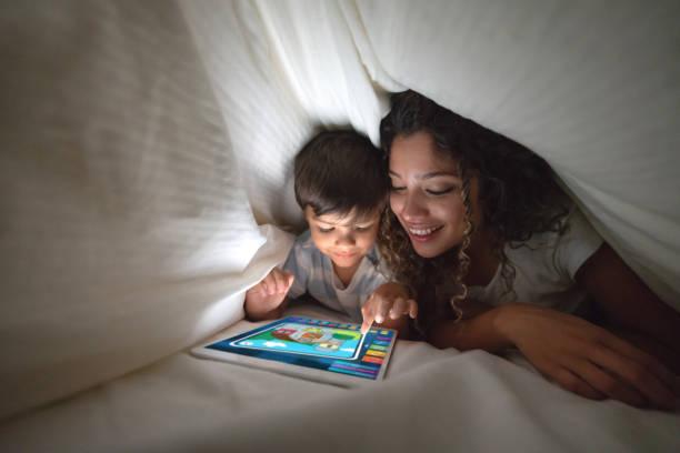 Mutter und Sohn spielen auf einem digitalen Tablet im Bett – Foto