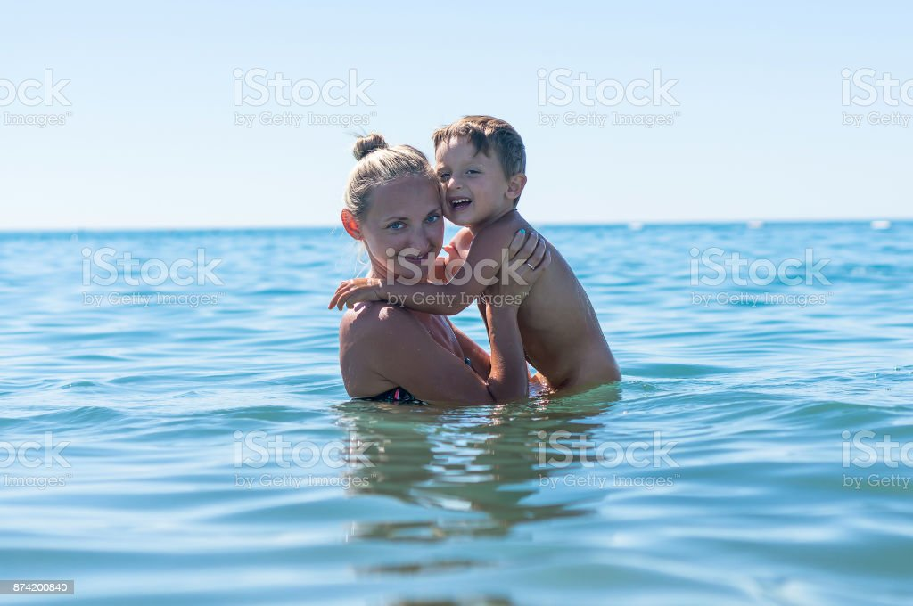 Mother and son playing on the beach in the day time. Portrait of happy little kid boy on the beach of ocean. Funny cute child making vacations and enjoying summer. Spring holidays. stock photo