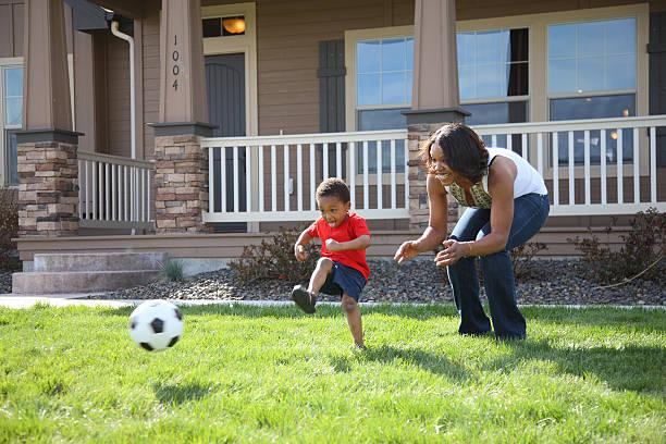 mutter und sohn spielt fußball - mutter kind heim stock-fotos und bilder