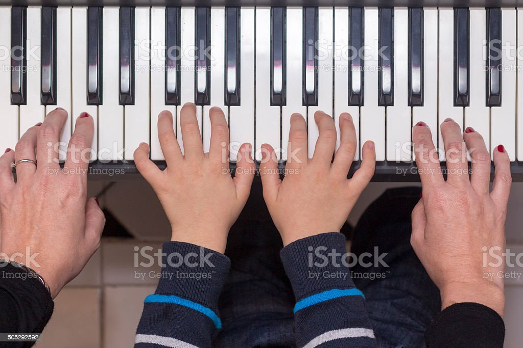 Mother and son playing the piano stock photo