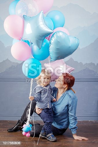 609058672 istock photo Mother and son playing with balloons. Concept of happy family. Birthday of the kid 1017580606