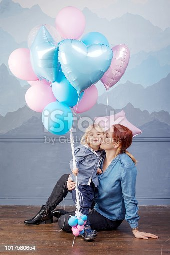 609058672 istock photo Mother and son playing with balloons. Concept of happy family. Birthday of the kid 1017580654