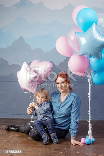 609058672 istock photo Mother and son playing with balloons. Concept of happy family. Birthday of the kid 1017580688