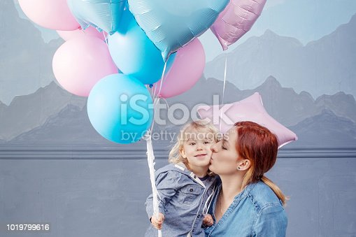 609058672 istock photo Mother and son playing with balloons. Concept of happy family. Birthday of the kid 1019799616
