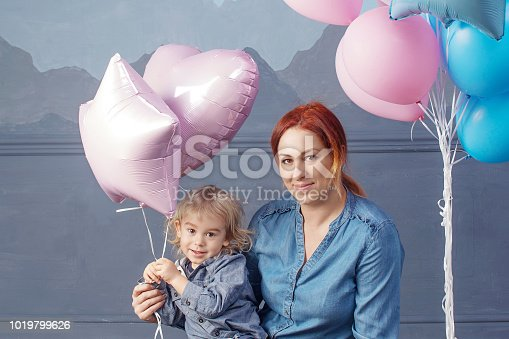 609058672 istock photo Mother and son playing with balloons. Concept of happy family. Birthday of the kid 1019799626