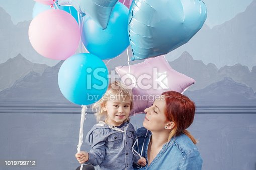 609058672 istock photo Mother and son playing with balloons. Concept of happy family. Birthday of the kid 1019799712
