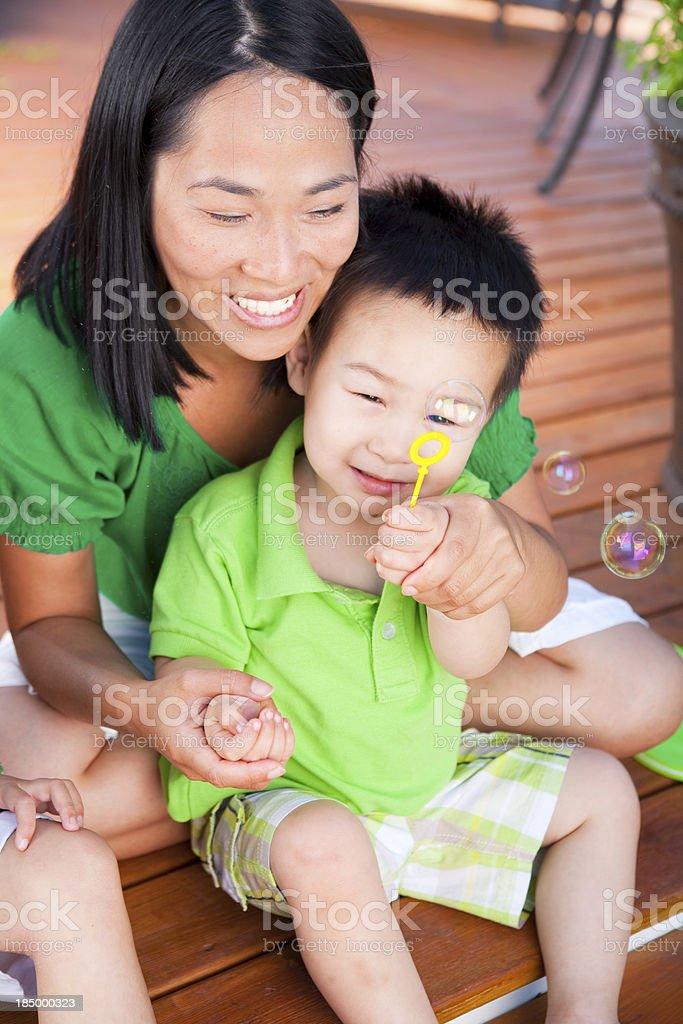 Mother and son playing with bubbles royalty-free stock photo
