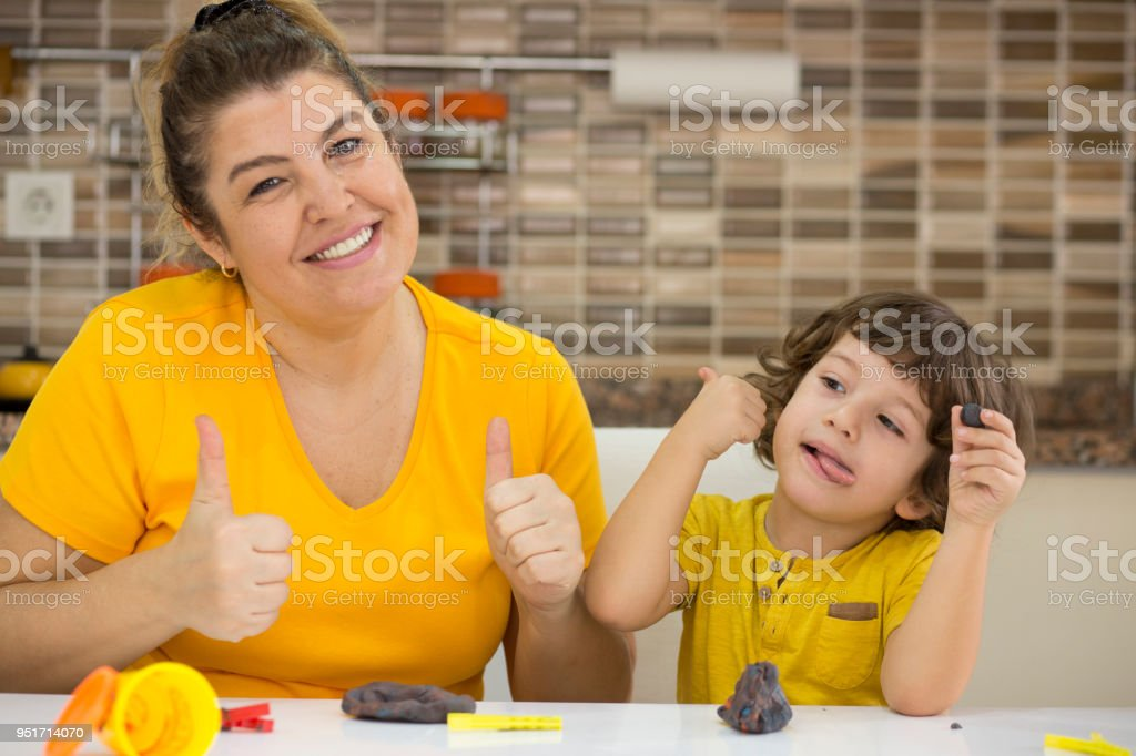 Mother And Son Playing With Childs Play Clay At Home Stock