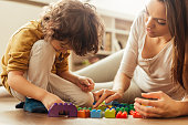 Close up of a young woman and her son playing with colourful blocks