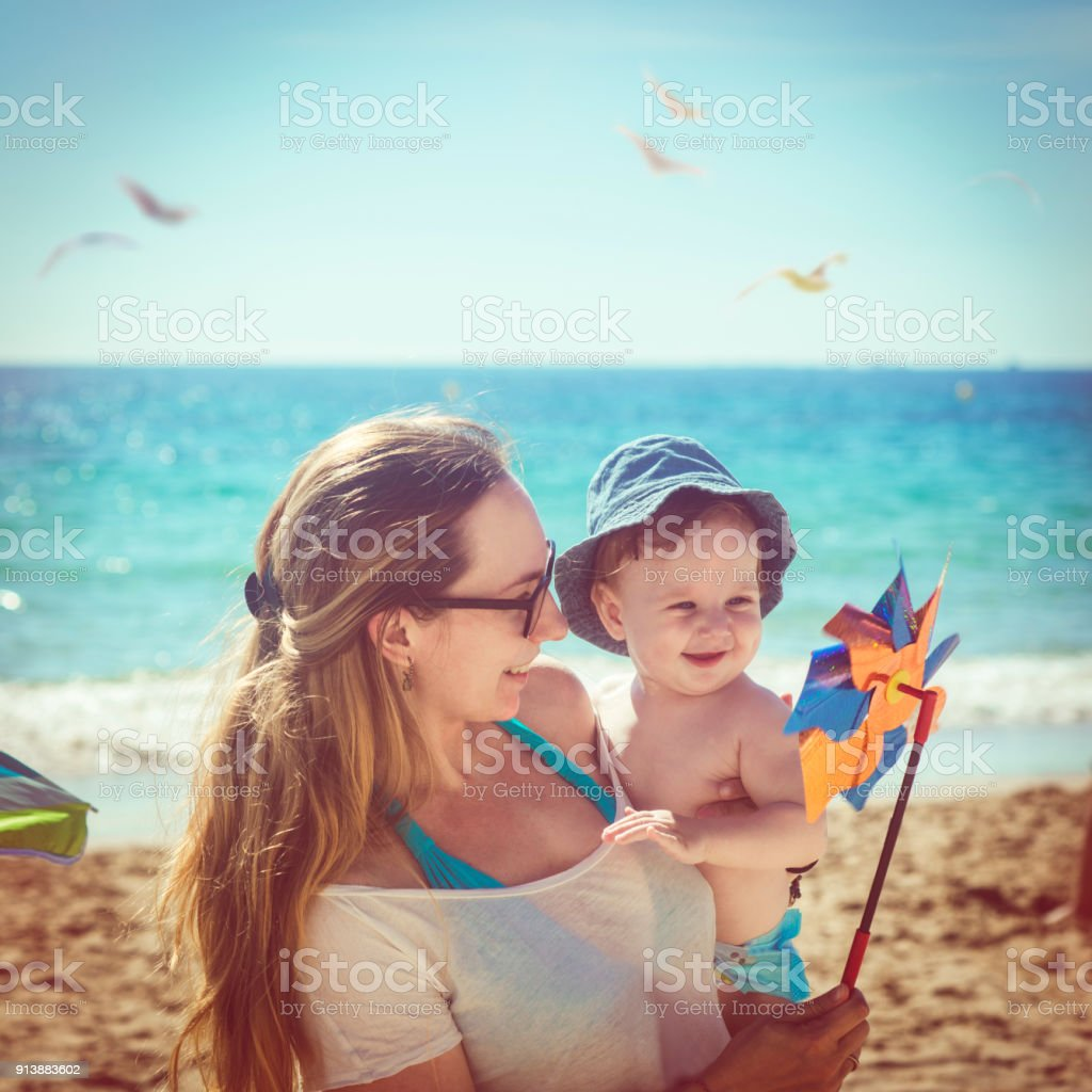 Mother and son playing with pinwheel on the beach stock photo