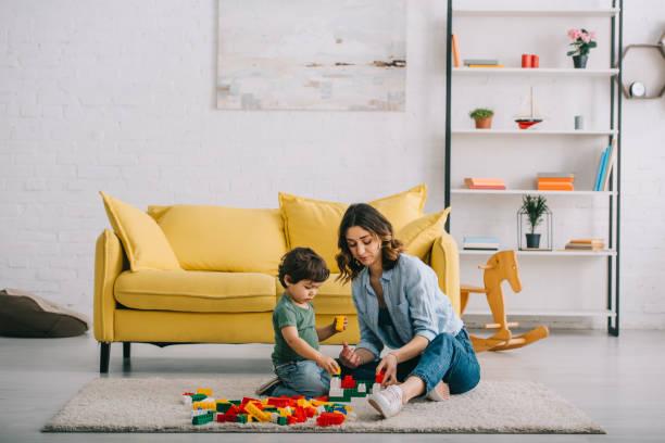 Mutter und Sohn spielen mit Lego auf Teppich im Wohnzimmer – Foto