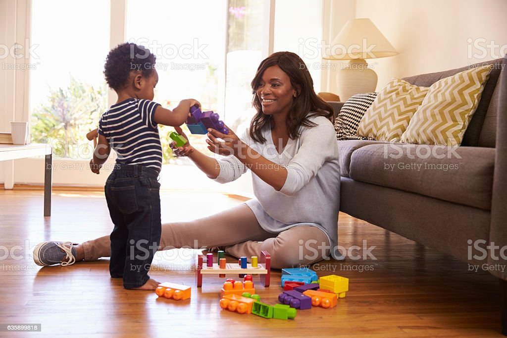 Mother And Son Playing With Toys On Floor At Home - foto de stock