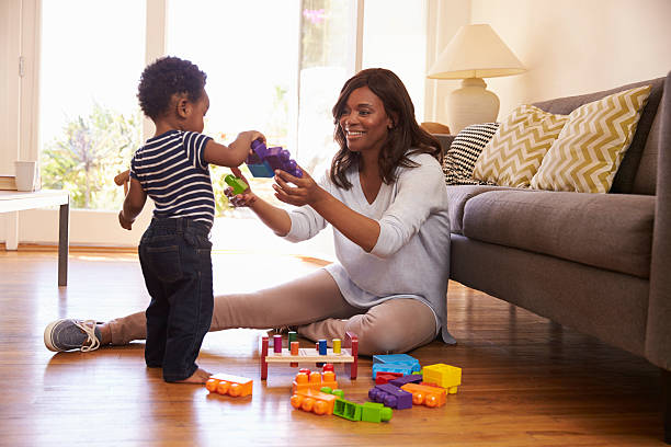 Mother And Son Playing With Toys On Floor At Home stock photo