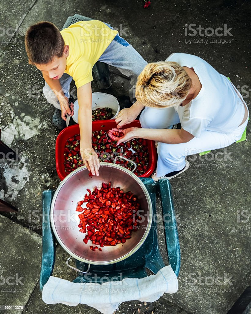Mother and Son preparing strawberries for making jam zbiór zdjęć royalty-free