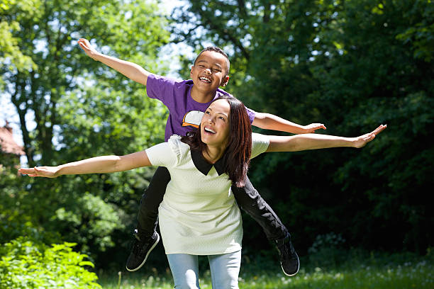 Mother and son pretending to fly stock photo
