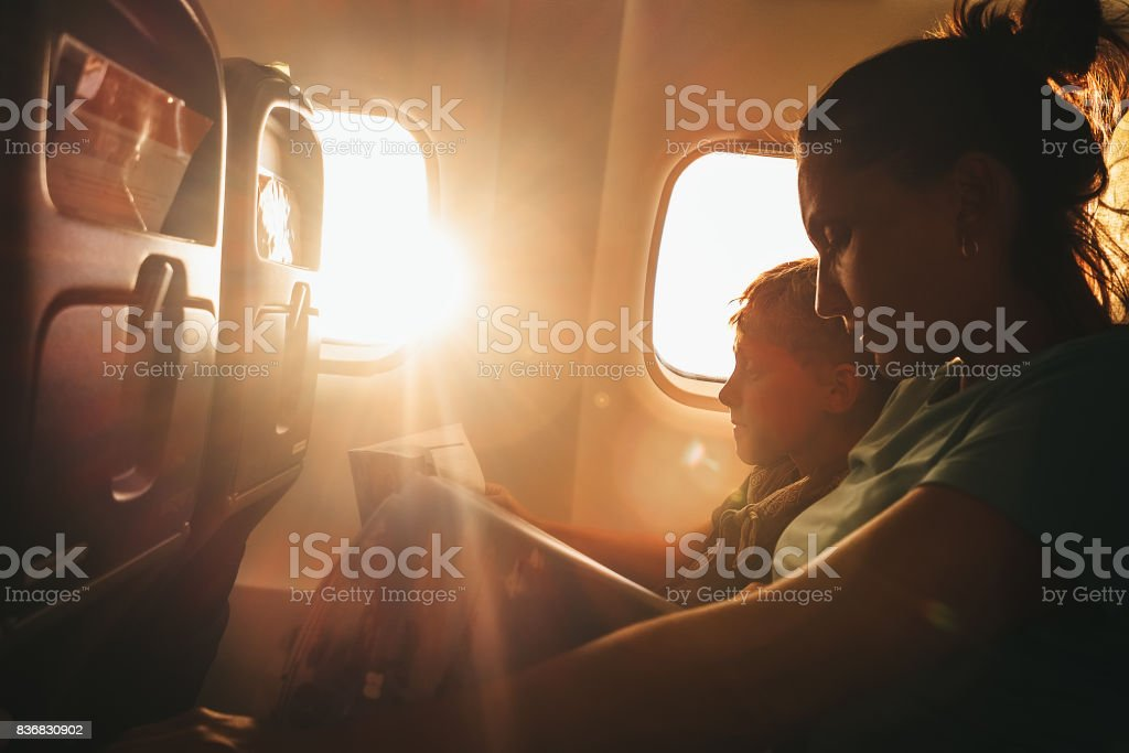 Mother and son read a books during fly stock photo