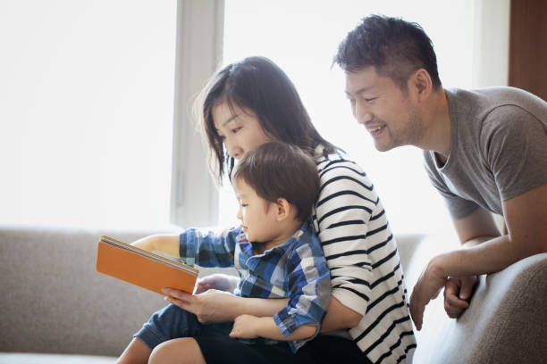 母と父はそれを見て、一緒に本を読んで息子 - 家族 日本人 ストックフォトと画像