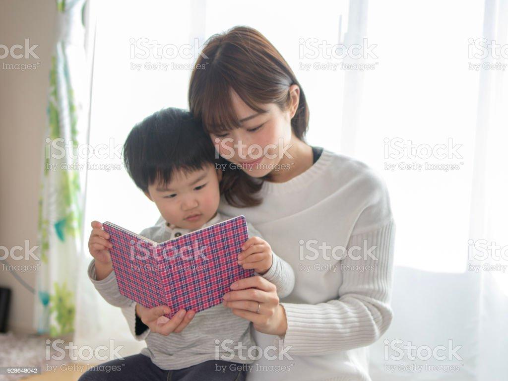 母親和兒子在客廳看書圖像檔