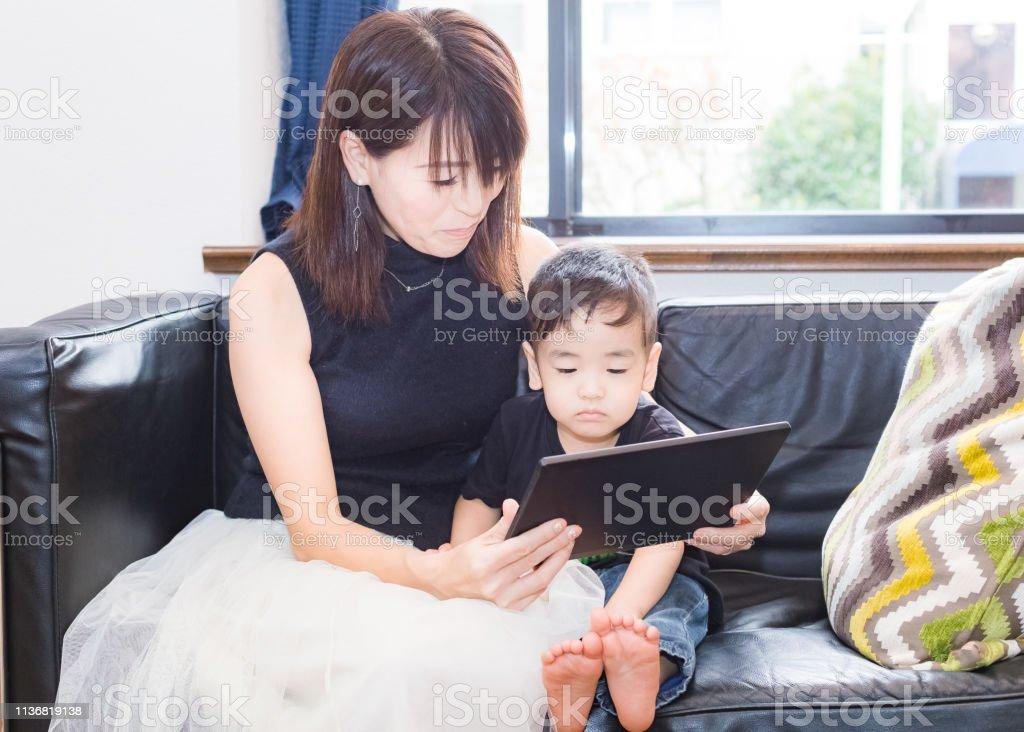 タブレットからの母と息子の読書 ストックフォト