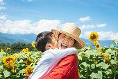 母と息子は太陽の花畑でリラックス