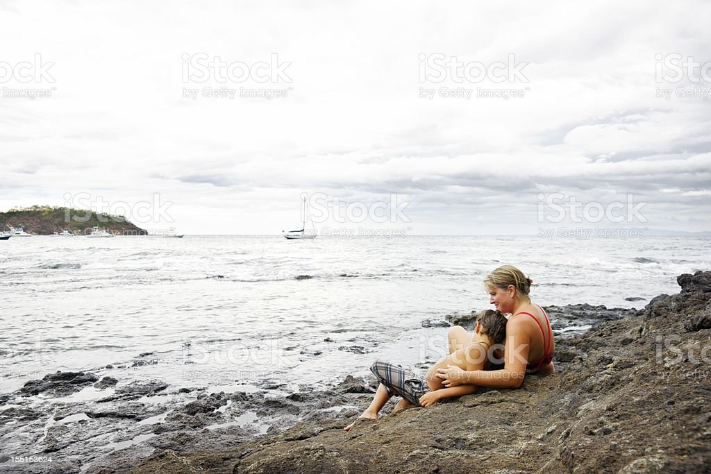 Mother and son relaxing by the sea stock photo
