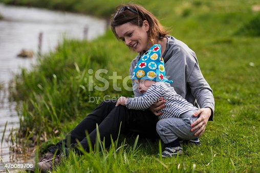 Mother and son resting on a lake bank
