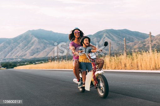 A mother and son enjoy a summer ride on a rural Utah road. They are loving the carefree, fresh air of the afternoon sun. Road trip.