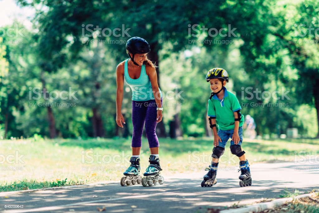 Mother and son roller skating in park stock photo
