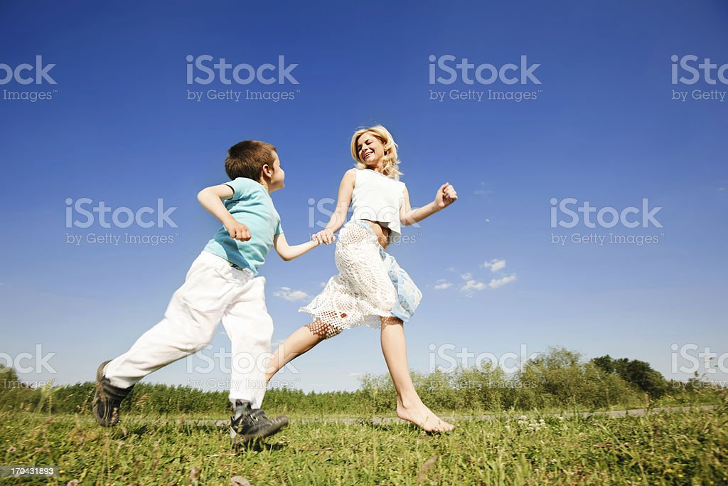 Mother and son running in the nature. royalty-free stock photo