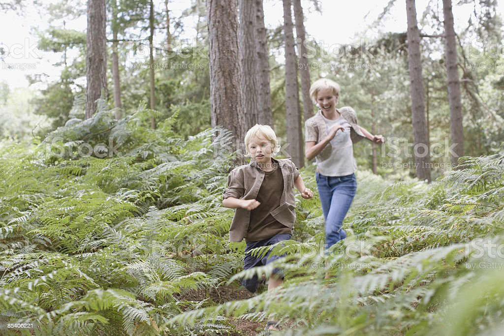 Mother and son running in woods royalty-free stock photo