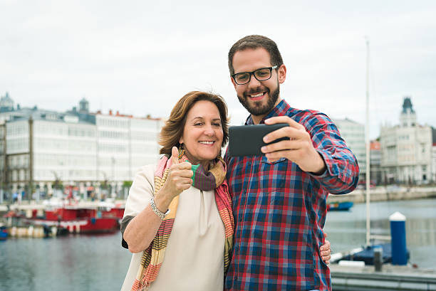 Mother and son selphie picture at urban harbour giving thumb stock photo
