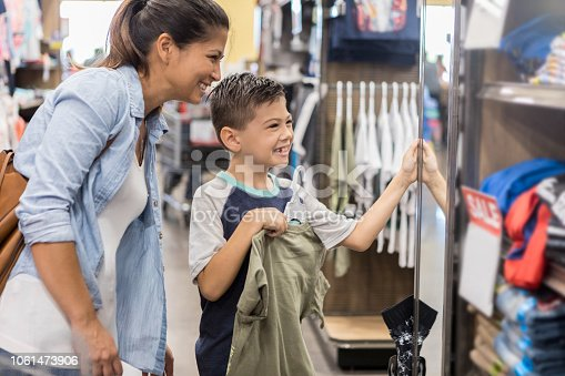 A mother lets her son pick out a new shirt while shopping after school.
