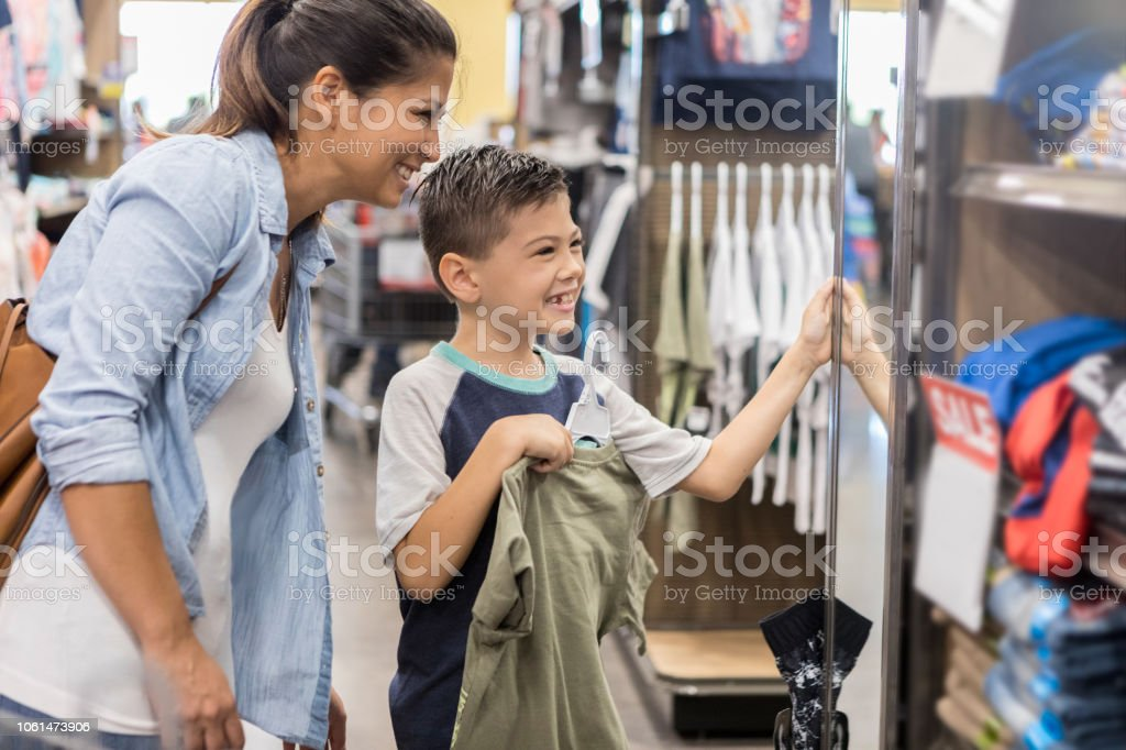 A mother and son shop for new clothes after school stock photo
