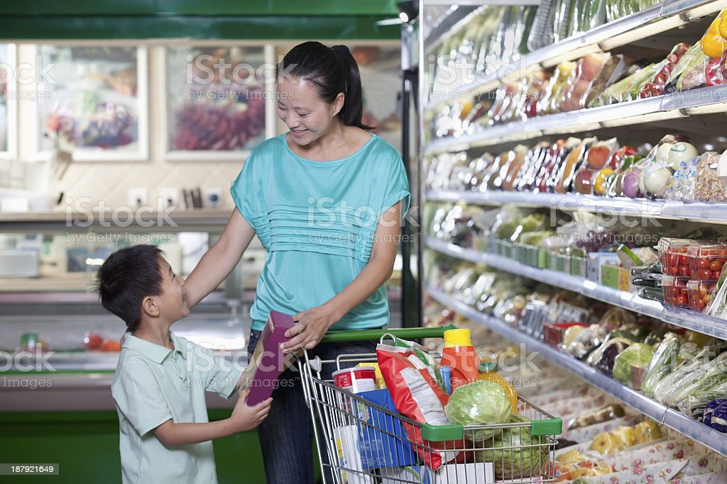Mother and son shopping for groceries in supermarket, Beijing stock photo