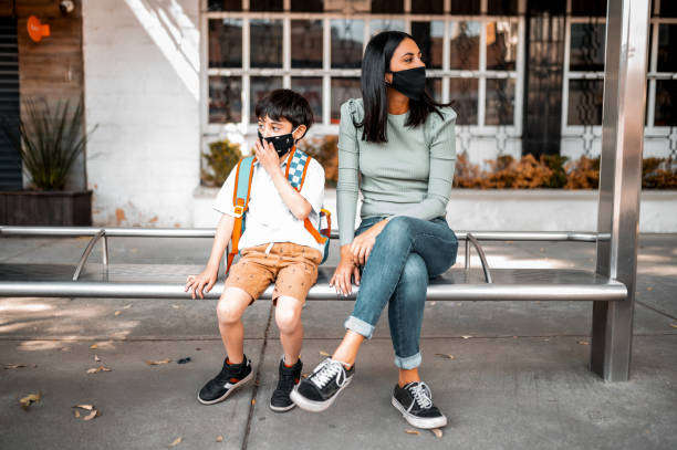 Mother and son sitting at the bus station stock photo