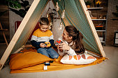 Mother and son sitting in a tent in their room and enjoying themselves