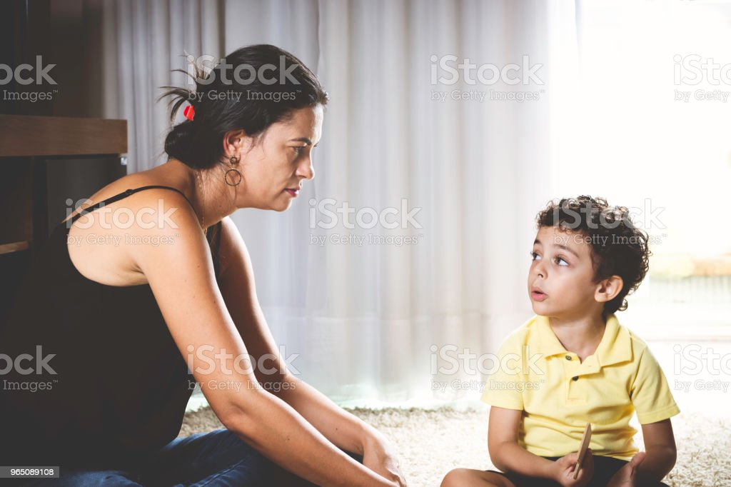 Mother and son sitting on the floor playing. zbiór zdjęć royalty-free