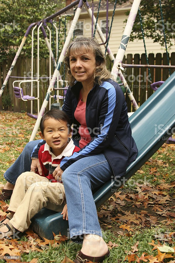 Mother and son sitting on the slide in backyard royalty-free stock photo
