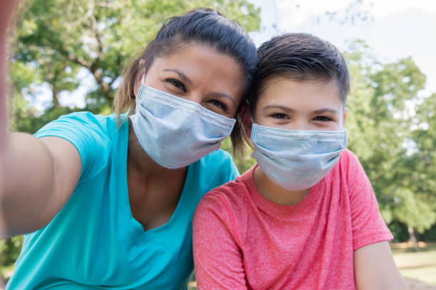 Mother and son smile under their masks for selfie stock photo