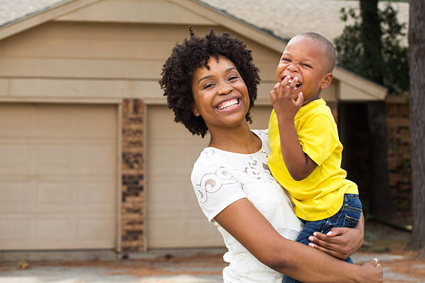 Mother and son standing in front of their new home. stock photo