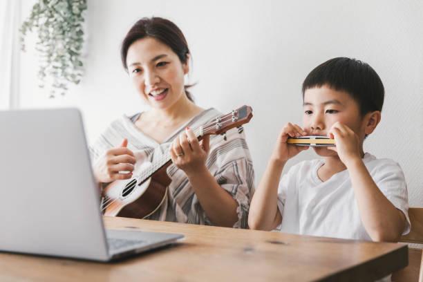 Mãe e filho tendo aula de música online em casa - foto de acervo