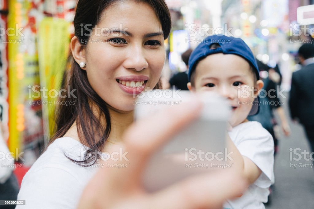 Mother and son taking selfie picture outdoors, cityscape on background stock photo