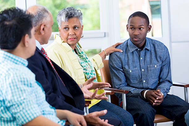 mother and son talking about behavior issues in group setting - family meeting stock photos and pictures