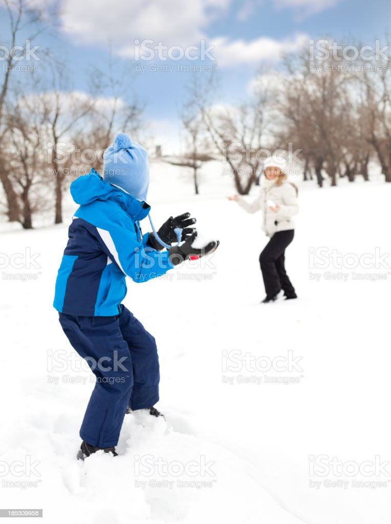 Mother and son throwing snowballs royalty-free stock photo