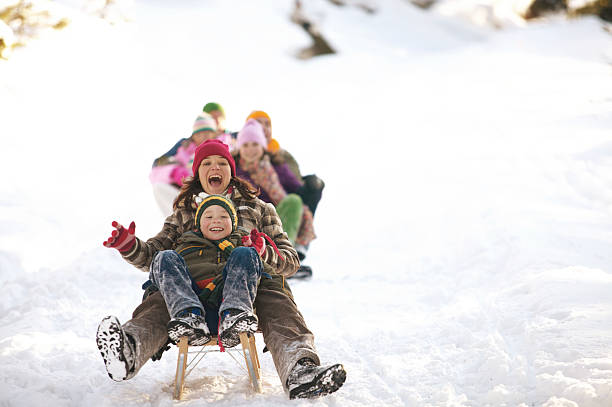 Mother and son (8-10) tobogganing in snow, family in background stock photo