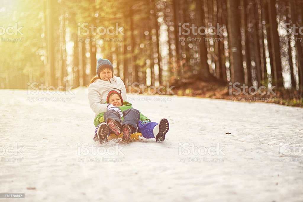Mother and son tobogganing stock photo